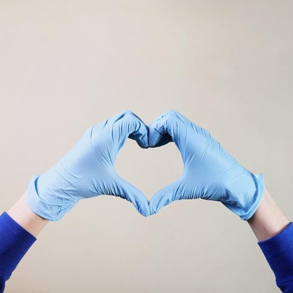 hands wearing blue nitrile gloves forming heart shape