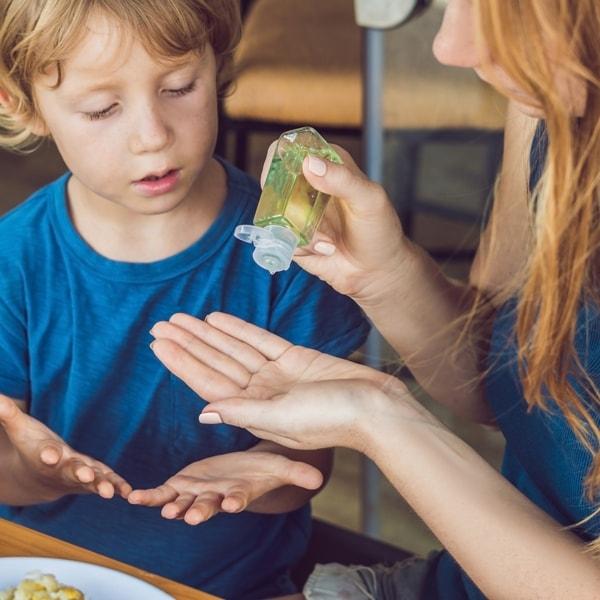 woman dispenses hand sanitizer gel to boy